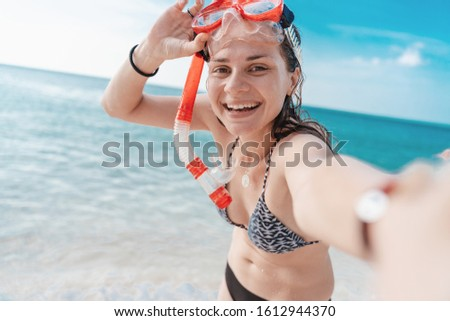 Young beautiful happy charming girl with a beautiful smile in a bikini in a mask for snorkeling takes a selfie on the seashore, outdoor activities, beach activities.