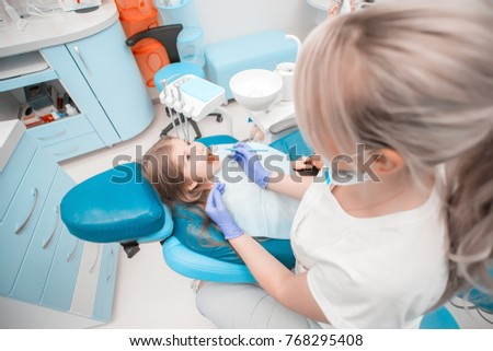 Young beautiful happy dentist doctor treats girl kid's teeth with special stomatological tool in a stomatology. A half length portrait of a female and cheerful kid with open mouth looking up.