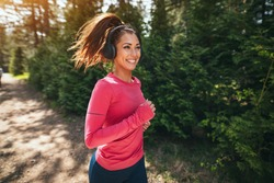 Young beautiful happy female runner listening to music while jogging along a sunny trail in forest.