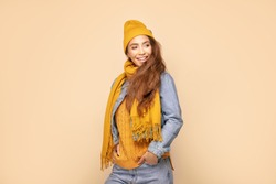 Young beautiful happy girl posing in studio wearing fashionable scarf, cap and jeans jacket. Smiling woman looking at camera. Human emotions,, expression. Beige studio background.