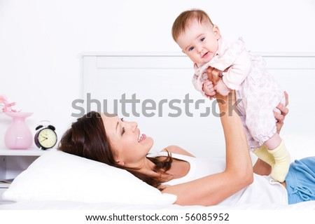 Young beautiful happy mother playing with her newborn baby - indoors