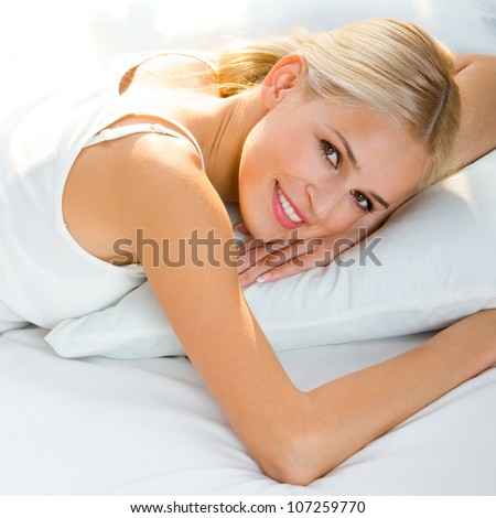 Young beautiful happy smiling blond woman waking up on bed
