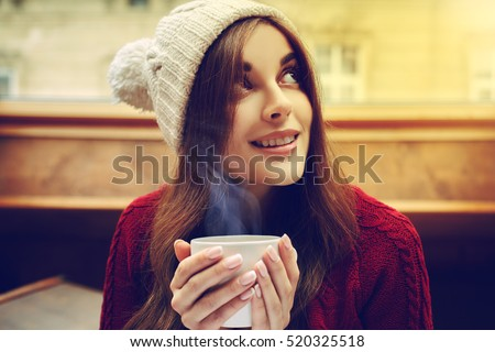 Young beautiful happy smiling girl holding white mug with hot liquid, drinking coffee or tea. Model wearing stylish knitted winter clothes, accessories. Lady looking up. Indoor. Close up. Toned
