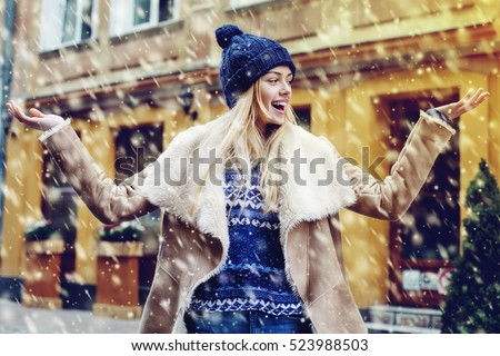 Young beautiful happy smiling girl posing on street. Model spread out her hands, catching snowflakes. Woman wearing stylish winter clothes. Magic snowfall effect Christmas, new year concept. Waist up