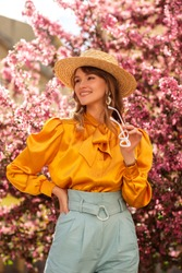 Young beautiful happy smiling woman wearing trendy wide brim straw hat, yellow satin blouse with bow tie, stylish blue high waist trousers, posing near pink spring blossom trees