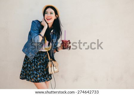 young beautiful happy stylish hipster girl, cocktail, smoozy drink, denim jacket, smiling, fashion, teen, cool accessories, purse, hat, sunglasses, amazed, vintage style, wall background, hair, wind stock photo