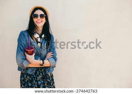young beautiful happy stylish hipster girl, cocktail, smoozy drink, denim jacket, smiling, fashion, teen, cool accessories, purse, hat, sunglasses, amazed, vintage style, wall background, hair, wind #274642763