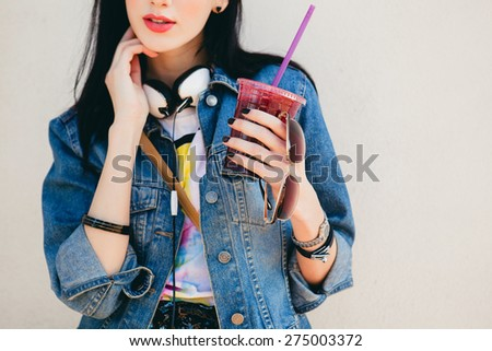 young beautiful happy stylish hipster girl, cocktail, smoozy drink, denim jacket, smiling, fashion, teen, cool accessories, purse, hat, sunglasses, vintage style, wall background, headphones, close up