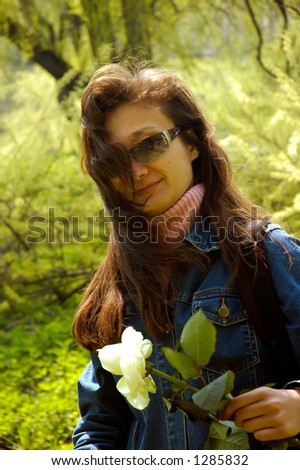 Young beautiful happy woman hiking in forest with a white rose