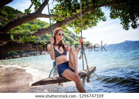 Young beautiful happy woman in top and shorts swinging on a swing on the shore of a tropical sea during vacation. Travel and vacation concept #1296747109