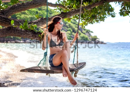 Young beautiful happy woman in top and shorts swinging on a swing on the shore of a tropical sea during vacation. Travel and vacation concept #1296747124