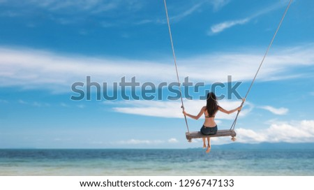 Young beautiful happy woman in top and shorts swinging on a swing on the shore of a tropical sea during vacation. Travel and vacation concept #1296747133
