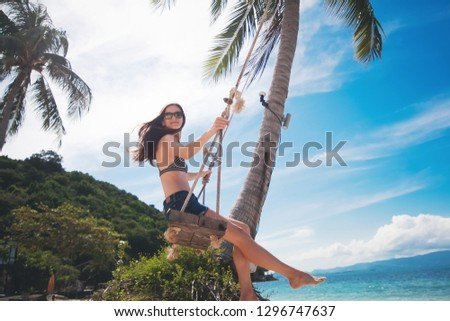 Young beautiful happy woman in top and shorts swinging on a swing on the shore of a tropical sea during vacation. Travel and vacation concept #1296747637