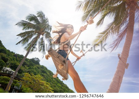 Young beautiful happy woman in top and shorts swinging on a swing on the shore of a tropical sea during vacation. Travel and vacation concept #1296747646