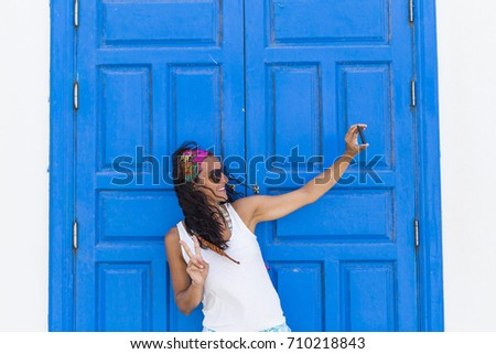 young beautiful happy woman taking a selfie with her mobile phone over a blue door background. Summer. Lifestyle