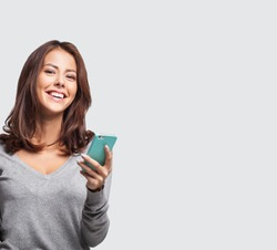 Young beautiful happy woman using smart phone. Excited surprised girl texting on her mobile phone. Studio shot isolated on grey background. Technology, connection, communication, apps concept