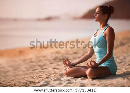 Young beautiful healthy woman making meditation on the beach, sunset on the sea.