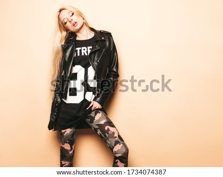 Young beautiful hipster bad girl in black leather jacket and stylish fashionable tight military pants leggings.Model with earring in nose.Sexy carefree  woman posing in studio