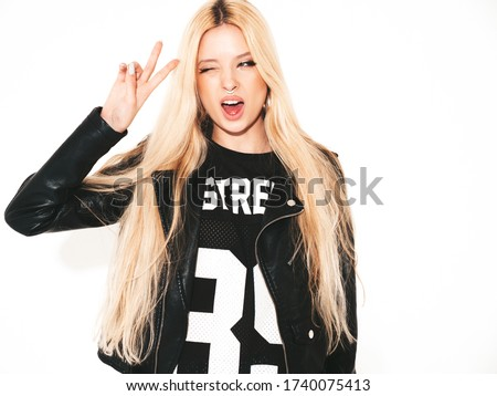 Young beautiful hipster bad girl in black leather jacket and stylish fashionable tight military pants leggings.Model with earring in nose.Sexy carefree  woman posing in studio.Isolated on white