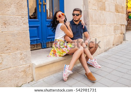 young beautiful hipster couple in love sitting on old city street, summer Europe vacation, travel, fun, happy, smiling, sunglasses, trendy outfit, romance, date, embracing, legs, sneakers #542981731