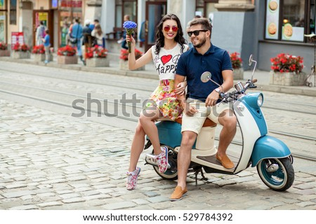 young beautiful hipster couple riding on motorbike city street, summer europe vacation, traveling, romance, smiling, happy, having fun, sunglasses, stylish outfit, together in love, adventures, date #529784392