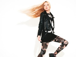 Young beautiful hipster girl in black leather jacket and stylish fashionable tight military pants leggings.Model with earring in nose.Sexy woman walking and jumping in studio.Flying hair in motion
