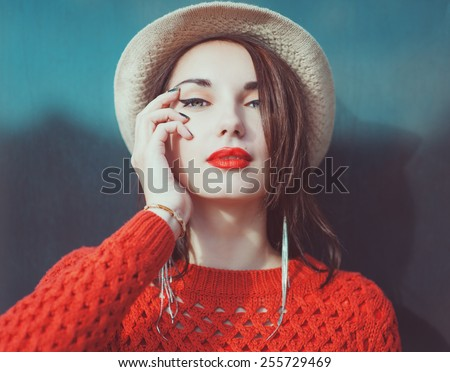 Young beautiful hipster girl in red jersey with hat outdoor