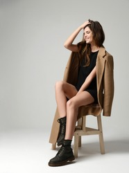 Young beautiful hipster girl sitting on chair thinking in little sexy dress brown spring jacket and modern stylish boots happy smiling on gray background