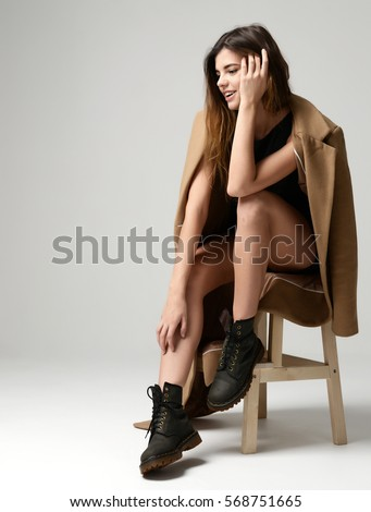 Young beautiful hipster girl sitting on chair thinking in little sexy dress brown spring jacket and modern stylish boots on gray background #568751665