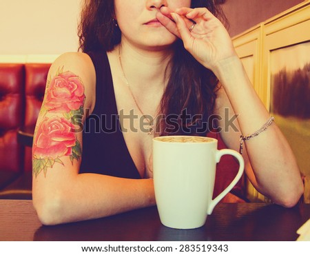 young beautiful hipster tattooed  woman with red curly hair at the bar with cup of coffee. Vintage style picture
