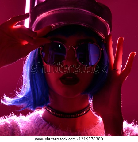 Young beautiful hipster woman in street style fashion winter concept wearing gold hat cap and round sunglasses in pink neon light