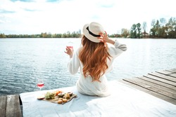Young beautiful hipster woman in trendy summer sundress and hat. Carefree woman making picnic outside. Positive model sitting on blanket, eating fruits, drinking rose wine