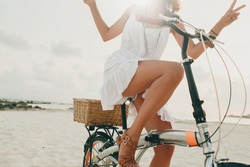 young beautiful hipster woman in white dress, tropical vacation, summer trend style, beach, riding bicycle, travel, Thailand, slim, tanned skin, positive, close-up details of legs, cheerful