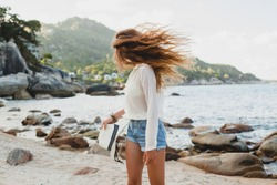 young beautiful hipster woman on summer vacation in asia, having fun on tropical beach, casual boho style, sea landscape background, slim tanned body, travel alone, long hair, smiling, happy, positive