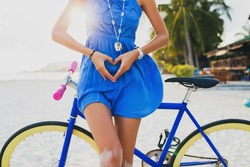young beautiful hipster woman posing with bicycle on beach, showing heart with hands, gesture, concept, details, summer vacation, vintage style, boho outfit, blue dress, slim body, bright, colorful