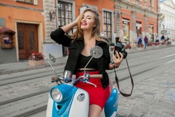 young beautiful hipster woman riding with photo camera on motorbike city street, taking pictures, summer europe vacation, traveling, smiling, happy, having fun, stylish outfit, adventures,