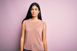 Young beautiful hispanic fashion woman wearing casual sweater over pink background with serious expression on face. Simple and natural looking at the camera.