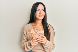 Young beautiful hispanic girl holding mexican pesos smiling looking to the side and staring away thinking.