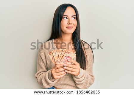 Young beautiful hispanic girl holding mexican pesos smiling looking to the side and staring away thinking.  Foto stock ©
