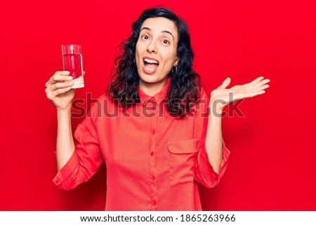 Young beautiful hispanic woman drinking glass of water celebrating achievement with happy smile and winner expression with raised hand  Stock foto ©