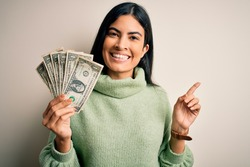 Young beautiful hispanic woman holding a pack of one dollar bunch of dollars very happy pointing with hand and finger to the side