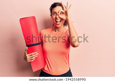 Young beautiful hispanic woman holding yoga mat smiling happy doing ok sign with hand on eye looking through fingers