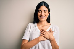 Young beautiful hispanic woman wearing casual white t-shirt over isolated background smiling with hands on chest with closed eyes and grateful gesture on face. Health concept.