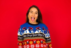 Young beautiful hispanic woman wearing Christmas sweater against red background  with happy and funny face smiling and showing tongue.