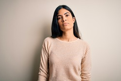 Young beautiful hispanic woman wearing elegant pink sweater over isolated background Relaxed with serious expression on face. Simple and natural looking at the camera.