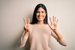 Young beautiful hispanic woman wearing elegant pink sweater over isolated background showing and pointing up with fingers number seven while smiling confident and happy.