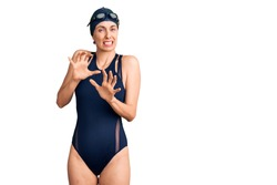 Young beautiful hispanic woman wearing swimwear and swimmer glasses disgusted expression, displeased and fearful doing disgust face because aversion reaction. with hands raised