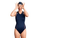 Young beautiful hispanic woman wearing swimwear and swimmer glasses doing ok gesture like binoculars sticking tongue out, eyes looking through fingers. crazy expression.