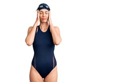 Young beautiful hispanic woman wearing swimwear and swimmer glasses with hand on head for pain in head because stress. suffering migraine.