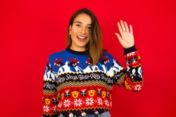 Young beautiful Hispanic woman wearing winter sweater against red wall waiving saying hello or goodbye happy and smiling, friendly welcome gesture.